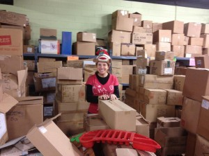 photo by catherine mayhew of betsy everett among the donations to be sorted for last year's christmas giveaway